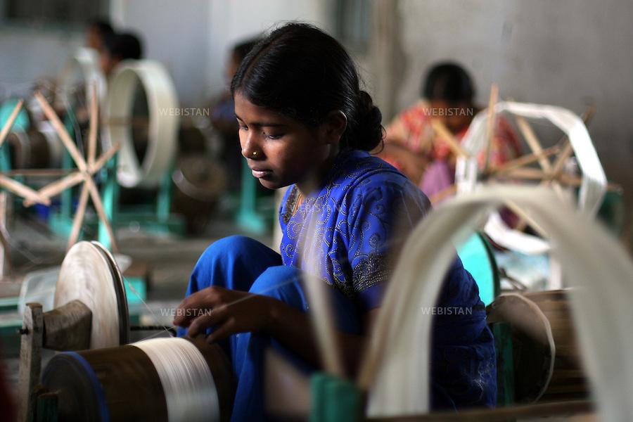 Bangladesh. Women weave the silk with a machine to make clothes. .Most of the silk produced by BRAC's beneficiaries is bought up by the Manikganj Foundation where the silk is dyed, and block printed and finally tailored into expensive kurtas and saris that are then sold through BRAC's sister-concern - the high-end designer store Aarong - which means bazaar. This is the final stage of a long process that began with the women who raise the silk-worms. ..Bangladesh. Des femmes tissent à l'aide d'une machine la soie pour confectionner des vêtements..La plupart de la soie produite par les bénéficiaires du BRAC est acheté par la Fondation Manikganj où la soie est teinte, puis imprimée en block et finalement taillée en de chers kurtas et saris qui sont ensuite vendus par le reseau de vente du BRAC, le Aarong. C'est l'étape finale d'un long processus qui a commencé avec des femmes qui élevent des vers à soie.
