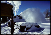 South-facing view of Chama water tank with rotary #OY throwing snow as it passes.<br /> C&amp;TS  Chama, NM  prior to 2/1978
