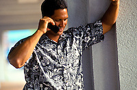 Young Hawaiian man in aloha shirt on cell phone