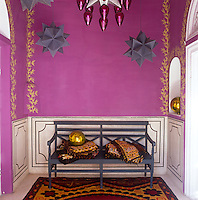 A small purple ante-room decorated with gold stencilling and grey-painted polyhedrons