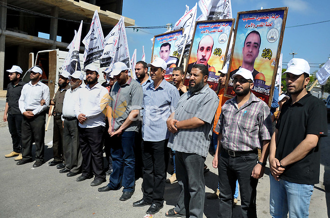 Palestinians take part in a demonstration in support of 125 Palestinian prisoners detained in Israeli jails and who have been on hunger strike for 50 days, outside Red Cross office, in Gaza City on June 11, 2014. 285 Palestinian prisoners are observing a mass hunger strike in protest against their being held without charge under a procedure called administrative detention. Of that number, 125 have been refusing food for more than six weeks, with 65 of them being treated in hospital, the Israeli Prisons Service said. Photo by Mohammed Talatene