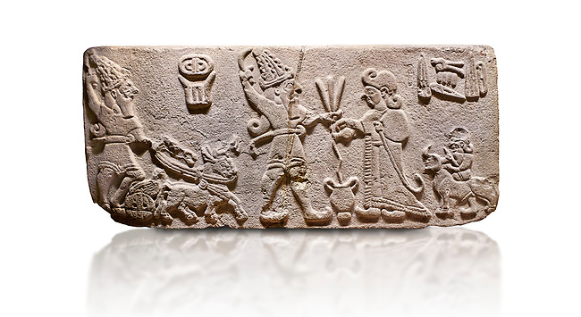 "Aslantepe Hittite Orthostat. Limestone, Aslantepe, Malatya, 1200-700 BC. Anatolian Civilizations Museum, Ankara, Turkey.<br /> <br /> Scene of offering drink and sacrifice. The god, with a symbol of divinity above, is in the chariot while holding a boomerang in his hand and a sword at his waist. The same god holds a lightning bundle in the middle. On the right, the king offers a drink to god. The inscription above reads ""Great, powerful King Sulumeli"". A servant stands behind holding a bull for sacrifice to the gods. <br /> <br /> Against a white background."