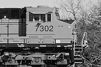 Closeup of moving locomotive, with the engineer visible at the helm.
