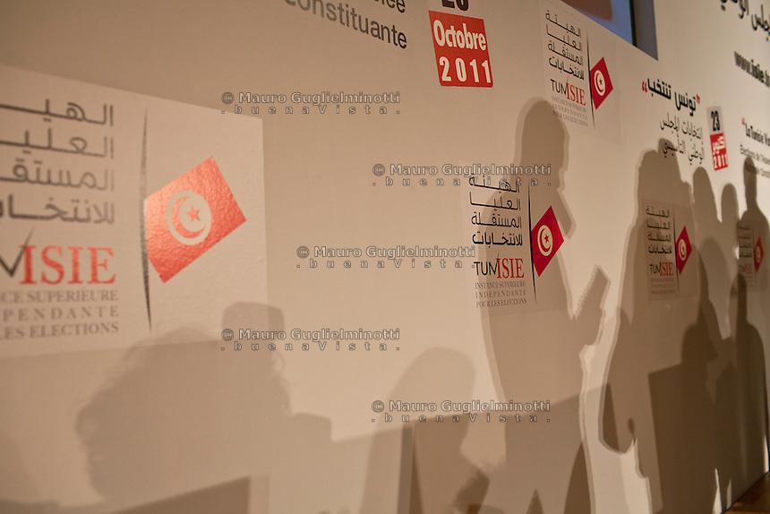 23 ottobre 2011 Tunisi, elezioni libere per l'Assemblea Costituente, le prime della Primavera araba: un muro con i simboli delle elezioni e le ombre di alcune persone.<br /> premieres elections libres en Tunisie octobre <br /> tunisian elections october