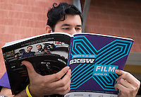 A South by Southwest attendee reads a SXSW Film program, Sunday, March 15, 2015, in Austin, Texas. (Darren Abate/M3D14.com)