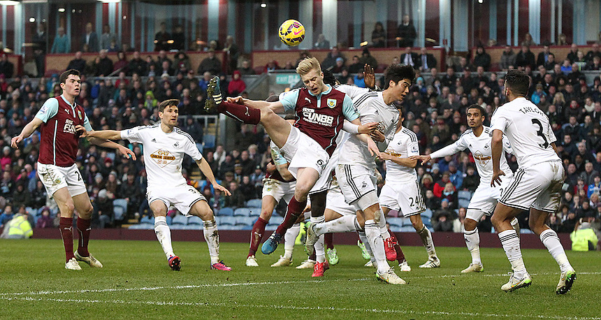 Burnley's Ben Mee battles for an aerial ball into the Swansea City penalty area with Ki Sung-Yueng<br /> <br /> Photographer Rich Linley/CameraSport<br /> <br /> Football - Barclays Premiership - Burnley v Swansea City - Friday 27th February 2015 - Turf Moor - Burnley<br /> <br /> &copy; CameraSport - 43 Linden Ave. Countesthorpe. Leicester. England. LE8 5PG - Tel: +44 (0) 116 277 4147 - admin@camerasport.com - www.camerasport.com