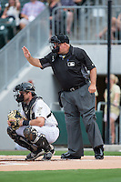 Home plate umpire Brian O'Nora signals for time as Charlotte Knights catcher Vinny Rottino (4) looks on during the game against the Pawtucket Red Sox at BB&T BallPark on July 6, 2016 in Charlotte, North Carolina.  The Knights defeated the Red Sox 8-6.  (Brian Westerholt/Four Seam Images)