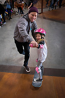 Khloe Parrott, 4, Phoenix, is guided by skate coach Neal Mims, San Diego,  on the ramps at 91 West Skatepark during Skate Rising for Girls.