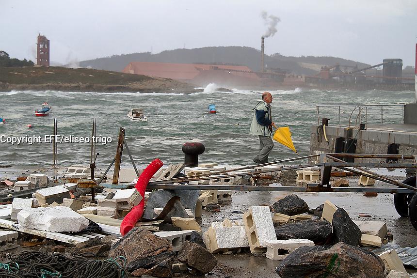 fecha: 09/11/2010 Temporal de viento. El puerto de San Ciprian en la costa de Lugo, resulto dañado por el fuerte oleaje. Las casetas de los pescadores quedaron destrozadas. En la imagen un hombre camina por el puerto, al fondo Alcoa.  Foto: EFE/eliseo trigo