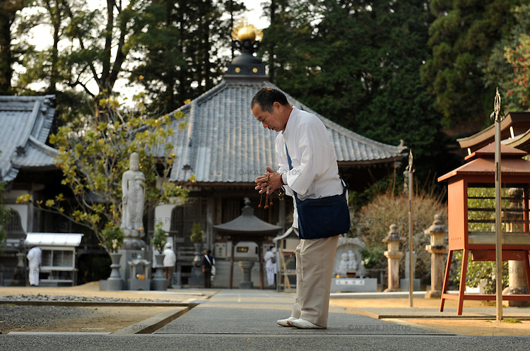 Henro pilgrim praying at a temple. Shikoku. Japan.