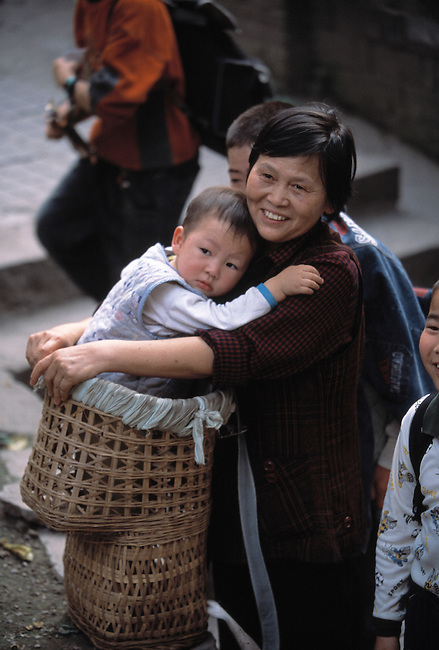 Mother and child embrace; smile; traditional carrying basket; city of Chongqing, China, Asia; 041603