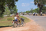 Cambodian woman drives away from Siem Reap school carrying school boy on motorbike