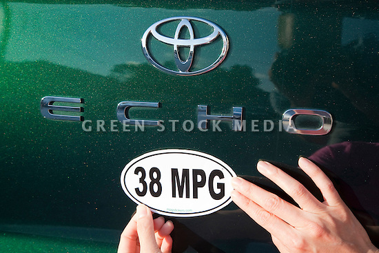 Close of a woman attaching a 38 miles per gallon fuel efficiency bumper sticker installed on Toyota Echo car. Sticker from MPG Stickers (mpgstickers.com), a grassroots, nonprofit campaign which aims to accelerate the adoption of fuel efficient vehicles in the United States. California, USA. Property released from mpgstickers.com.