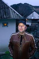 RUMAENIEN, 04.2013, Rosia Montana (Apuseni-Gebirge). Das kanadische Unternehmen Gabriel Resources versucht seit Jahren Europas groesstes Gold-Tagebau-Bergwerk mit Zyanid-Technologie zu eroeffnen. Verantwortlich vor Ort ist die Rosia Montana GOLD Corporation RMGC. Sorin Jurca von der Kulturstiftung Rosia Montana, einer der Leiter des Widerstandes gegen das Projekt, vor seinem Geburtshaus in der Oberstadt. | The Canadian company Gabriel Resources has been trying for years to open Europe's biggest open pit gold mine based on cyanide technology. The local subsidiary is the Rosia Montana GOLD corporation RMGC. Sorin Jurca of the Rosia Montana cultural foundation, one of the resistance leaders against the project, in front of the house he was born..© Martin Fejer/EST&OST