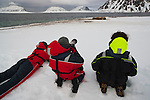 Norway, Svalbard, tourists lying in snow photographing walruses