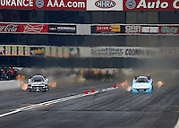 Feb 7, 2015; Pomona, CA, USA; NHRA funny car driver Cruz Pedregon (left) races alongside Tommy Johnson Jr during qualifying for the Winternationals at Auto Club Raceway at Pomona. Mandatory Credit: Mark J. Rebilas-