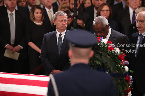 U.S. Supreme Court Chief Justice John Roberts looks over at Associate Justice Clarence Thomas, nominated to the Supreme Court by former President George H.W. Bush, as they stand before the late president's casket inside the U.S. Capitol Rotunda on Capitol Hill in Washington, U.S., December 3, 2018. REUTERS/Jonathan Ernst/Pool