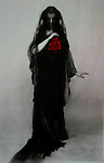 A woman in a long black dress with veil holding a red rose