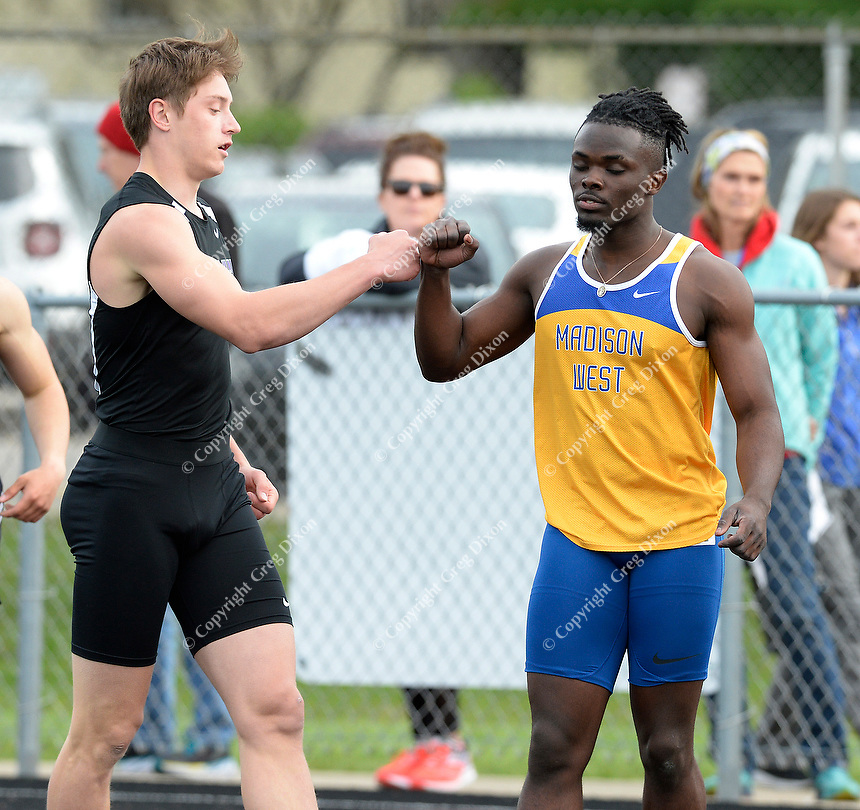 Waunakee's Sawyer Maly left fist bumps Madison West's Kelvin Opoku-Appoh after the 100 meter dash Monday night. Maly finishes first in the event, with a time of 11.06 seconds. Opoku-Appoh finishes second in 11.11 seconds.