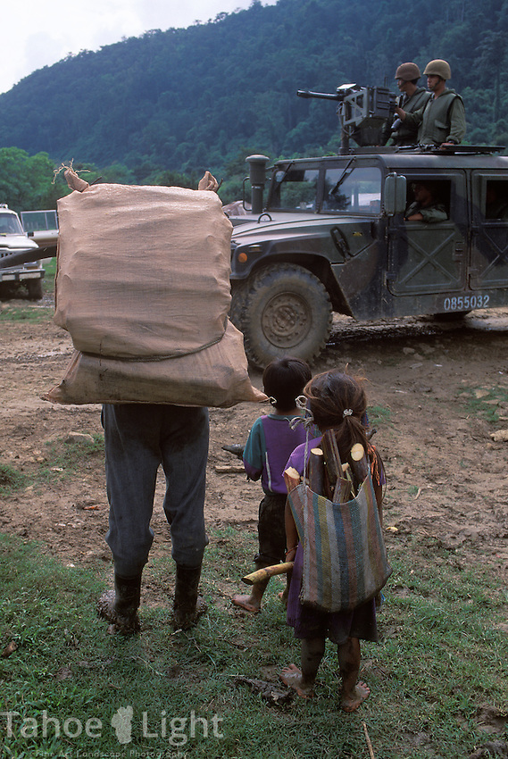 A Tzeltal Indian family brings back wood for cooking and sugar cane as they stop to watch an army patrol pass through their Zapatista Supporting town of La Realidad deep in the Jungles of chiapas