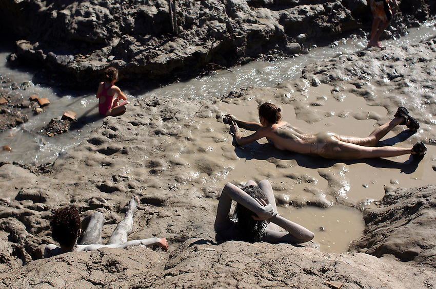 People covered in mud repose in the ancient Baths of sulphurous waters of Tiermas on October 13, 2012, in the Spanish reservoir of Yesa. The ancient baths of sulphurous waters of Tiermas are under Yesa reservoir waters and return to the surface when the reservoir is running low on water.  Photo: Ander Gillenea