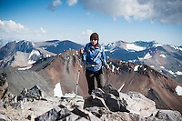 Female hiker on rocky summit of Mt. Dana (13,053 ft), Yosemite national park, California, USA