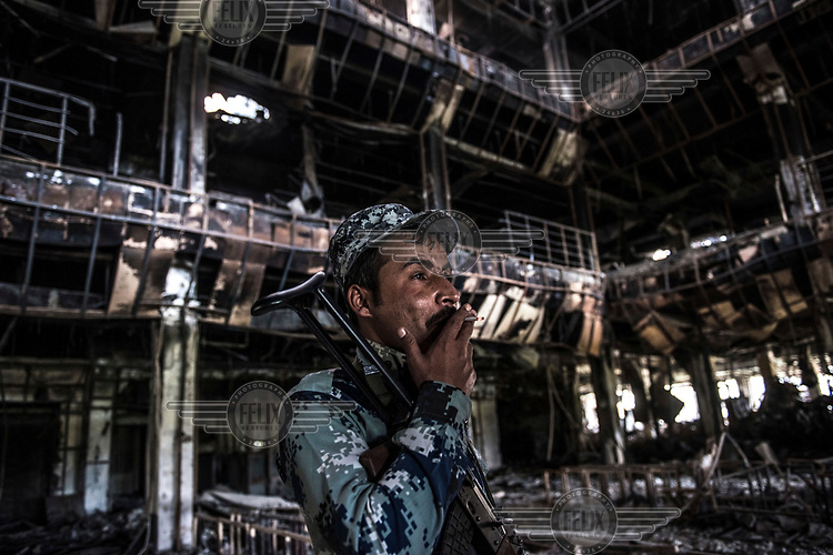 A Federal Policeman smokes a cigarette inside the charred remains of the University of Mosul's library which was burned out by ISIS militants who controlled the area until late 2016.