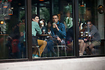 Customers at a Starbucks watch as protestors make their way through downtown Seattle during the Solidarity Against Hate rally Sunday August 13, 2017.