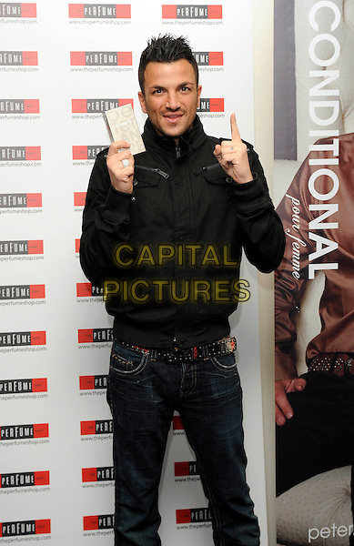 "PETER ANDRE.Attends a signing for ""Unconditional"" the now number one best selling fragrance at Bluewater Shopping Centre, Kent..10th December 2009..half length black jacket jeans holding box aftershave finger hand pointing gesture .CAP/DH.©David Hitchens/Capital Pictures."