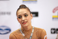 "Evgenia Kanaeva of Russia smiles at ""kiss & cry"" after her ribbon routine and on way to winning All-Around gold at 2008 European Championships at Torino, Italy on June 6, 2008.  Photo by Tom Theobald."