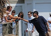 Oak Bluffs, MA - August 26, 2009 -- United States President Barack Obama greets other patrons during a  stop to pick up a a take-out lunch of fried seafood at Nancy's Restaurant in Oak Bluffs, Massachusetts on the island of Martha's Vineyard, Wednesday, August 26, 2009.  .Credit: Neal Hamberg - Pool via CNP