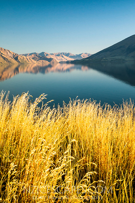 Perfect autumn reflections of mountains in mirror like Lake Wanaka, Central Otago, New Zealand