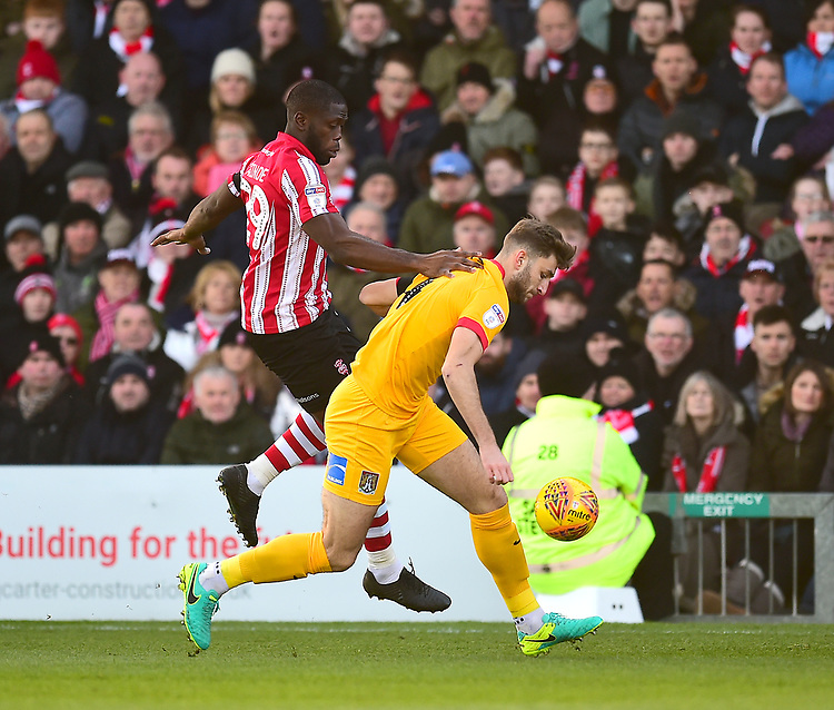 Lincoln City's John Akinde vies for possession with  Northampton Town's Charlie Goode<br /> <br /> Photographer Andrew Vaughan/CameraSport<br /> <br /> The EFL Sky Bet League Two - Lincoln City v Northampton Town - Saturday 9th February 2019 - Sincil Bank - Lincoln<br /> <br /> World Copyright &copy; 2019 CameraSport. All rights reserved. 43 Linden Ave. Countesthorpe. Leicester. England. LE8 5PG - Tel: +44 (0) 116 277 4147 - admin@camerasport.com - www.camerasport.com