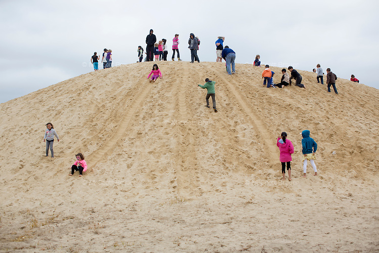 Children play on a sand dune during the AD Makepeace Company's 10th Annual Cranberry Harvest Celebration in Wareham, Massachusetts, USA. AD Makepeace is the world's largest producer of cranberries. These cranberries, wet harvested with varied colors, are destined for processing into juice, flavoring, canned goods and other processed foods. The sand is used to maintain root structure in cranberry bogs.
