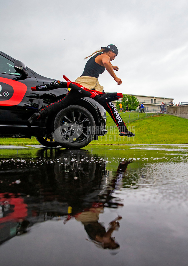 May 20, 2018; Topeka, KS, USA; NHRA top fuel driver Leah Pritchett jumps over a water puddle during a rain delay to the Heartland Nationals at Heartland Motorsports Park. Mandatory Credit: Mark J. Rebilas-USA TODAY Sports