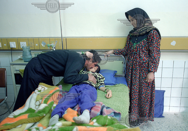 """(February 1998) Nine year old Haiman Sabri with his parents at the Saddam hospital in Baghdad. <br /> According to his doctor Haiman had a curable infection, but due to lack of anti biotics suffered life threatening complications.  <br /> Due to UN sanctions the hospital was lacking many medicines, and the civilians suffered due to lack of food as well. <br />  Former U.N. Humanitarian Coordinator in Iraq Denis Halliday estimated the resulting deaths : """"Two hundred thirty-nine thousand children 5 years old and under"""" as of 1998.<br /> <br /> The sanctions against Iraq were a near-total financial and trade embargo imposed by the United Nations Security Council on the Iraqi Republic.<br /> <br /> <br /> ©Fredrik Naumann/Felix Features"""