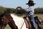 A young cowboy getting the rope ready to throw from horseback