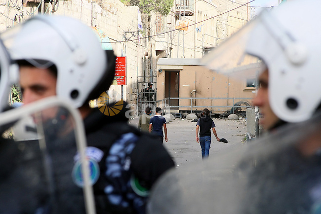 Palestinian riot police stand guard to prevent protesters during clashes with Israeli soldiers in the West Bank City of Hebron, on September 24, 2013. Jewish Settlers held a protest tent in front of a house of the Palestinian Abu Rajab family, after the order of Israeli Prime Minister Benjamin Netanyahu of the disputed Machpela house, a Hebron structure near the Cave of the Patriarchs from which he had removed 15 Jewish settlers last year, following the killing of an Israeli soldier. Photo by Mamoun Wazwaz
