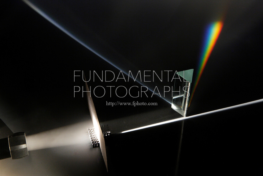 WHITE LIGHT IS REFRACTED BY A TRIANGULAR PRISM<br /> Forming a spectrum of its component colors<br /> The light source passes through a slit that focuses the light to precisely hit the prism, refracting into a spectrum. The spectral dispersion of light through the prism is projected onto the background.
