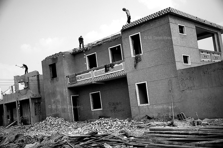 Workers break away bricks and concrete to find rebar and other metals for salvage in Nanjing, Jiangsu, China.Workers demolish residential buildings in a small suburban village east of Nanjing, Jiangsu Province, China.