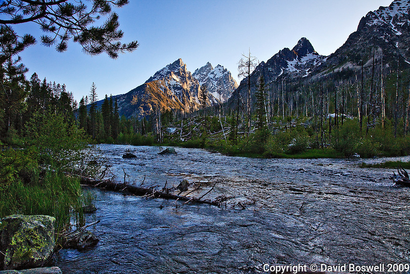 The mouth of Cascade Canyon and the Cathedral Group above it can be seen in the light of the setting sun in Grand Teton National Park.  The Cathedral Group consists of Teewinot, Mount Owens, and Grand Teton, the highest peak in the Tetons.