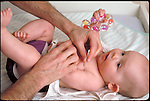 hands taking axillary temperature of infant