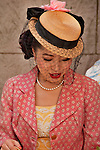 A girl in the New York City Easter Parade wearing a yellow dress, pink jacket, and a small straw hat with a delicate black net over her face