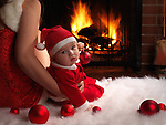 Mother and a little baby boy sitting in front of a fireplace in Christmas costumes.