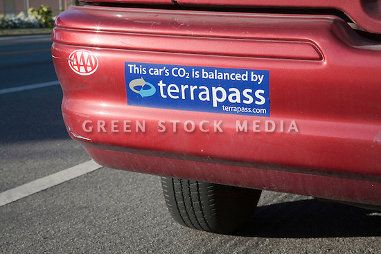 A bumper sticker on a red car declaring the purchase of carbon offsets for the car's carbon emissions. TerraPass is a carbon offset company serving individuals and businesses. Palo Alto, California, USA