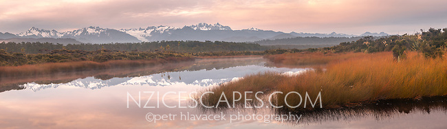 Pastel colours of pink dawn over Five Mile lagoon with Southern Alps in background. Mt. Cook, Mt. Tasman and Franz Josef Glacier, Westland NP, West Coast, New Zealand