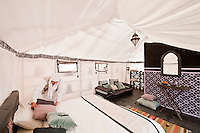 A room attendant plumps up cushions on a bed in one of the tents of this luxury camp