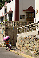 Woman carrying a parasol crossing Angel Flores Street  with a young school child  in old Mazatlan, Sinaloa, Mexico