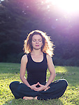 Woman meditating in the nature sitting on grass in sunlight