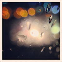 The lights of traffic in my rearview mirror reflect in the rain drops on my car window on January 11, 2013.